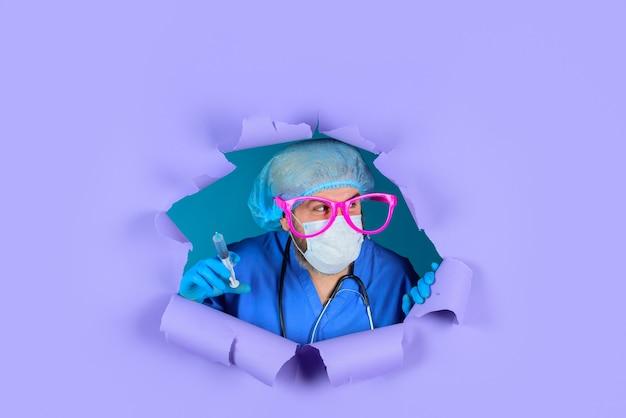 Vacinação para pessoas vacinação médico em copos grandes com seringa olhando através do papel