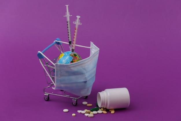 Vacinação. tratamento de pandemia global. carrinho de compras com máscara médica, globo, pílulas e seringas em fundo roxo