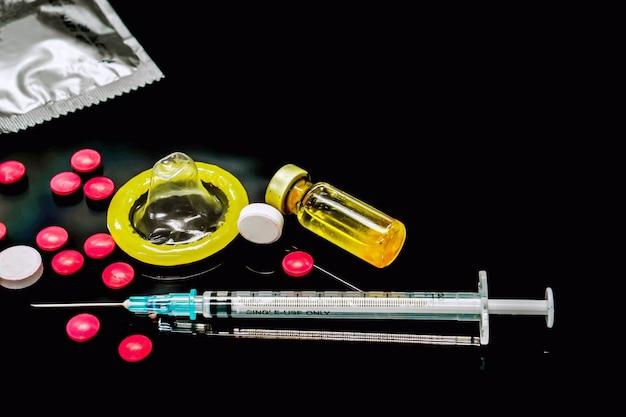 Vacinas em frascos, medicamentos brancos e vermelhos com uma seringa de plástico e preservativos isolam em fundo preto. amostra do que causou a infecção pelo hiv. e o preservativo é para prevenir a infecção.