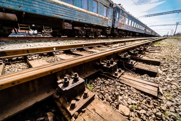 Vagão azul velho no close up dos trilhos. travessas de madeira ou laços transversais.