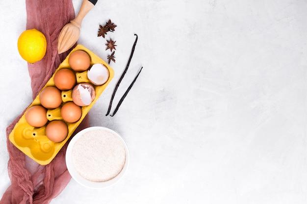 Vagem de baunilha; ovos; limão; anis estrelado; farinha e espremedor de madeira no fundo texturizado branco
