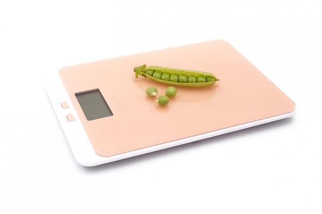 Vagem de ervilha verde fresca com as sementes em escalas da cozinha no branco. o conceito de pesagem.