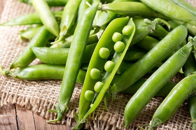 Vagem de ervilhas verdes frescas na mesa de madeira