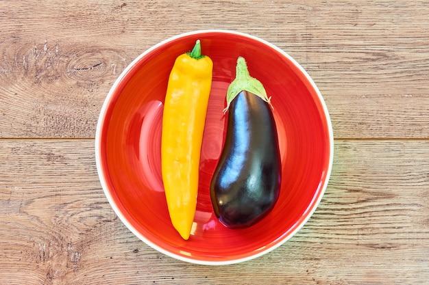 Vagem de pimenta amarela e berinjela quase preta em uma placa vermelha em uma mesa de madeira