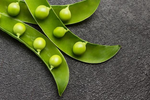 Vagens abertas de ervilhas verdes na mesa. fundo preto. postura plana