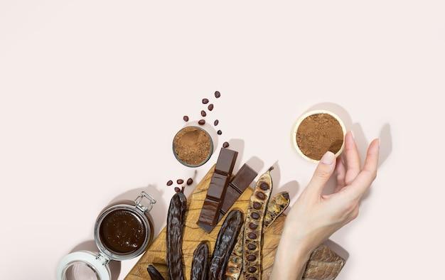 Vagens de alfarroba orgânica em pó com chocolate e melaço de alfarroba em uma placa de madeira em uma mão de mulher em uma rosa