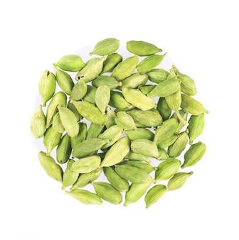Vagens de cardamomo isoladas no branco. sementes de cardamomo verde. traçado de recorte vista do topo.