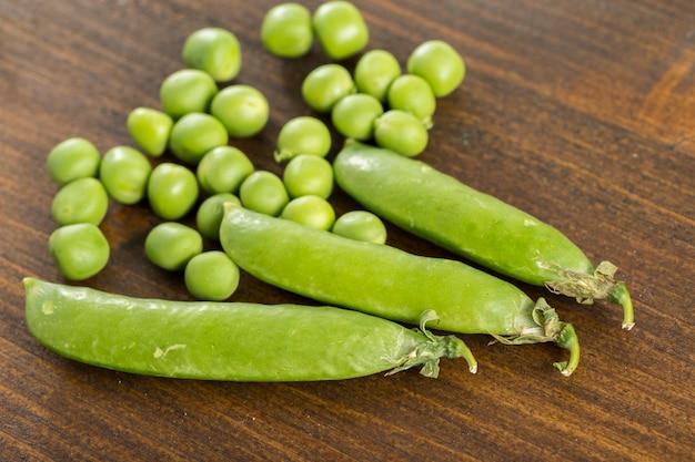 Vagens de ervilha e ervilhas em cima da mesa