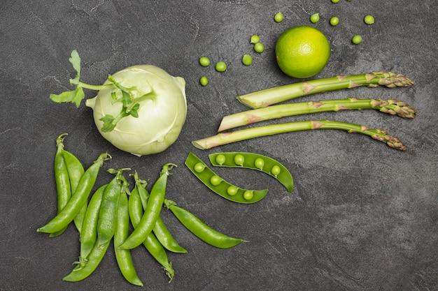 Vagens de ervilha verde, aspargo, couve-rábano e limão na mesa
