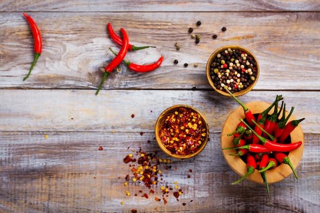 Vagens de pimenta malagueta vermelha em um pilão de madeira, flocos de pimenta e grãos de pimenta em bacias de madeira