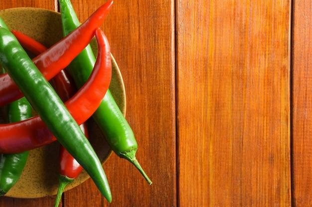 Vagens de pimenta verde e vermelha fresca estão à esquerda em um prato de cerâmica em uma mesa de madeira marrom