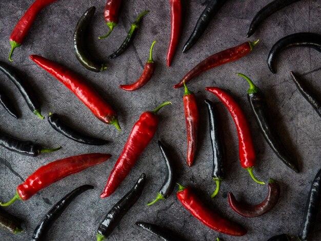 Vagens de pimenta vermelha e preta em fundo escuro de concreto