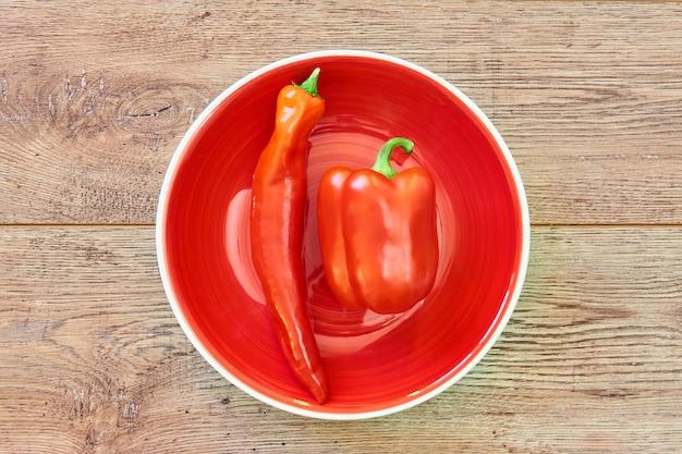 Vagens finas e grossas de diferentes variedades de pimentão em um prato vermelho sobre uma mesa de madeira