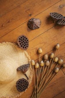 Vagens secas de lótus e sementes de papoula e chapéu de palha em um velho piso de madeira.