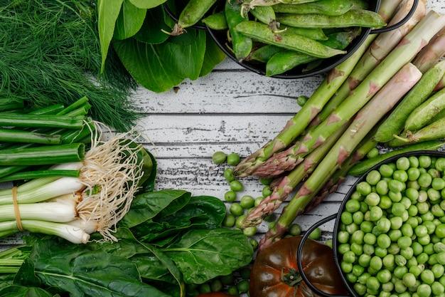 Vagens verdes, ervilhas com tomate, endro, azeda, aspargo, cebola verde, bok choy em panelas na parede de madeira, vista superior.