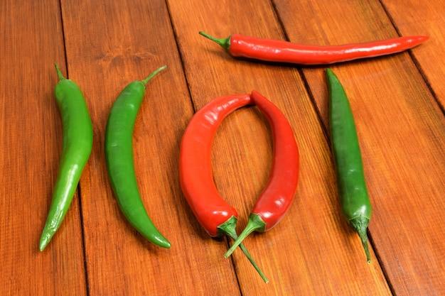 Vagens vermelhas e verdes de pimenta fresca exibiam a palavra quente em uma mesa de madeira marrom