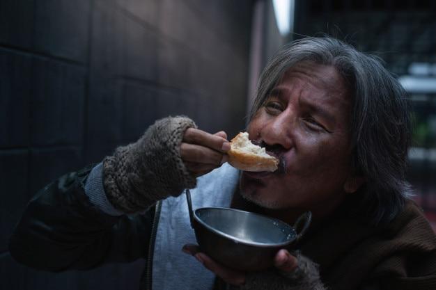 Vagrant asiática se sentir feliz com o pão e leite doados.