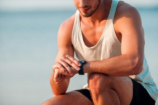 Vai bater seu melhor tempo. imagem recortada de jovem homem musculoso verificando as horas em seus relógios enquanto está sentado ao ar livre