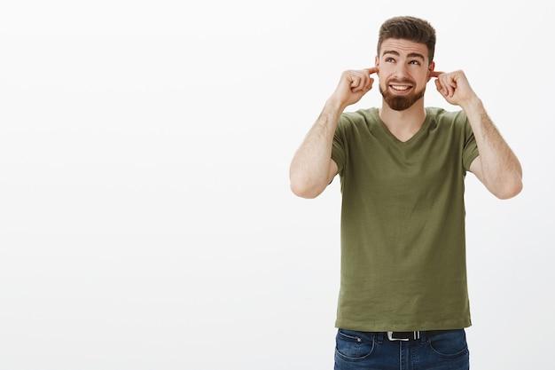 Vai ser alto. retrato de um cara barbudo bonito preparado para barulho e sons irritantes fecha os ouvidos com os dedos indicadores apertando os olhos e franzindo o nariz enquanto olha para fogos de artifício sobre a parede branca