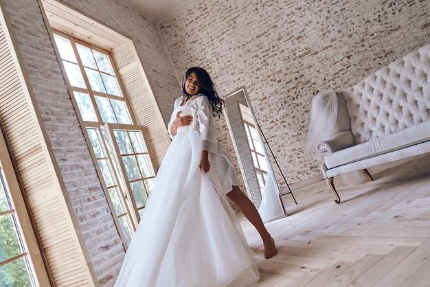 Vai ser um dia mágico. comprimento total de uma jovem atraente em um roupão de seda, experimentando seu vestido de noiva e sorrindo em pé