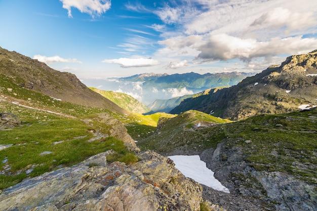 Vale alpino brilhante ao pôr do sol de cima