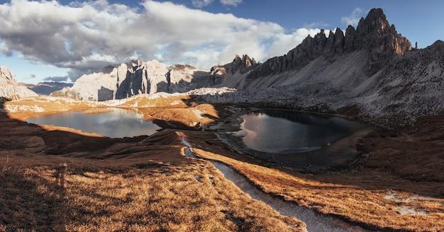 Vale com lagos nas montanhas majestosas dolomitas em dia ensolarado. foto panorâmica
