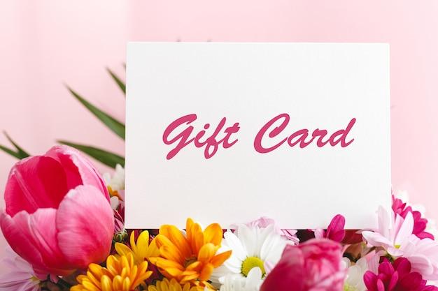 Vale-presente em buquê de flores em fundo rosa de flores de verão para mulher voucher surpresa