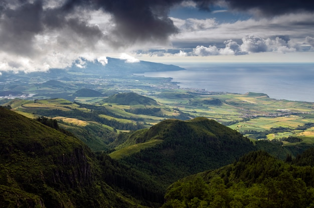 Vale verde agradável vista à beira-mar de montanhas altas com nuvens. são miguel. açores