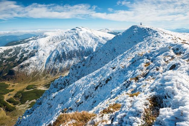 Vale verde e picos brancos de montanhas na neve. paisagem de inverno