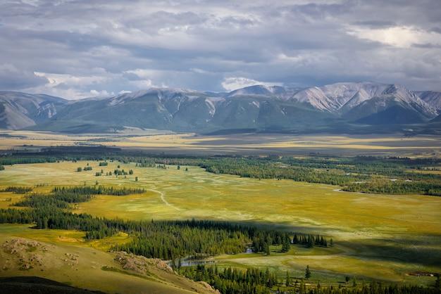 Vale verde pitoresco na luz do sol contra a cordilheira de neve sob céu nublado no verão ou outono.