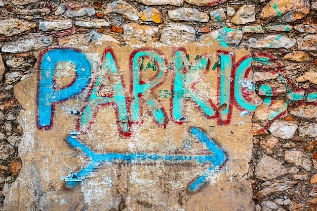 Valência, espanha - 14 de dezembro de 2018: sinal velho do estacionamento pintado em uma parede lascada.
