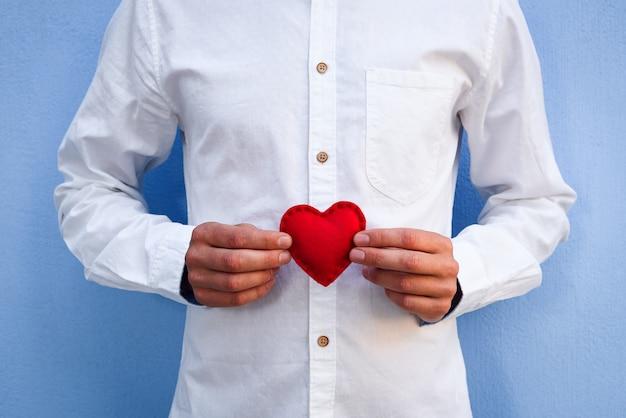 Valentim vermelho nas mãos de um cara em uma camisa branca contra uma parede azul. feliz dia dos namorados conceito