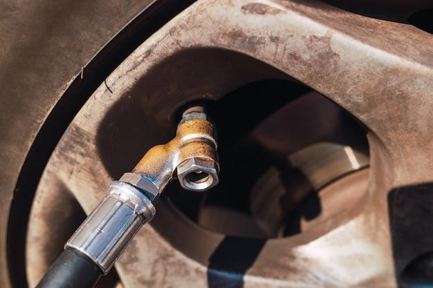 Válvula de ar de um pneu de carro ao lado do manômetro para inchar.