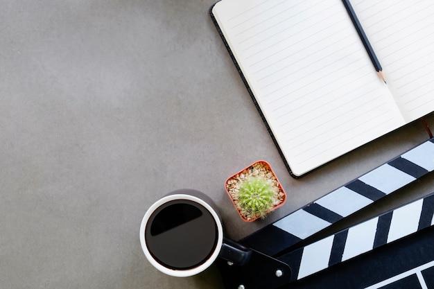Válvula do filme com papel do bloco de notas, xícara de café, cacto na opinião de tampo da mesa do diretor e espaço da cópia.