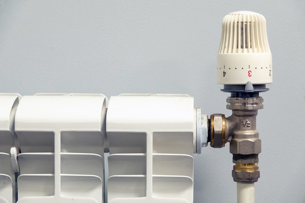 Válvula termostática em um radiador em fundo cinza