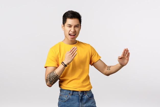 Vamos agitar esta festa. ousado e animado homem asiático tatuado segurando as palmas das mãos em gesto de luta, como se praticasse habilidades de combate, judô ou artes marciais, digamos sim, em pé de parede branca