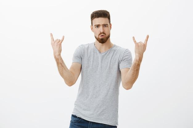 Vamos arrasar nessa festa. retrato de um modelo masculino, elegante e entusiasmado, com barba e bigode, mostrando o gesto de rock-n-roll, fazendo beicinho e carrancudo, curtindo show e música contra a parede branca