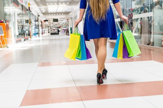 Vamos às compras, pernas femininas com sacolinhas de papel no shopping