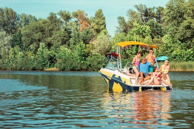 Vamos celebrar. grupo de jovens alegres celebrando seu encontro sentados no convés de um barco de recreio