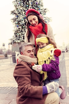 Vamos jogar. encantadora mulher de cabelos compridos baixando a cabeça enquanto olha para a filha