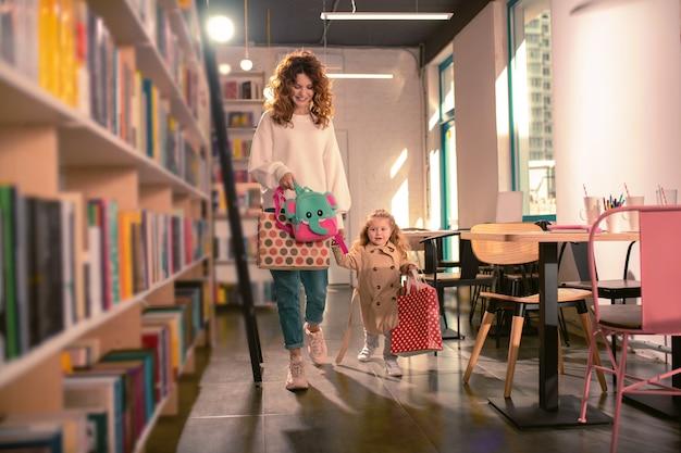 Vamos. mulher bonita se sentindo feliz e segurando sacolas de compras na mão direita