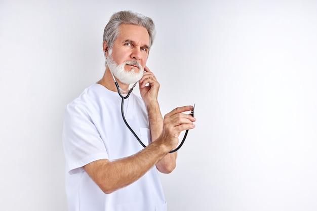 Vamos ouvir o seu batimento cardíaco, um velho e experiente médico usa um estetoscópio no trabalho, pronto para ajudar