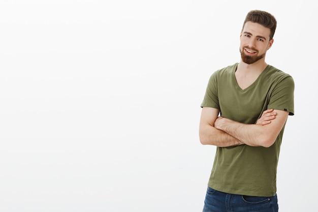 Vamos, pare de brincar, vamos ao que interessa. retrato de um cara barbudo, entusiasmado e bonito em pose confiante, as mãos cruzadas contra o corpo e sorrindo deliciado, assegurado sobre a parede branca