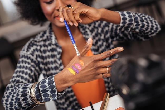 Vamos tentar. linda mulher de pele escura usando uma pulseira de ouro e colocando novas amostras na mão