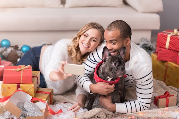 Vamos tirar uma selfie. homem bem parecido e feliz e emocional abraçando seu cachorro e sorrindo enquanto está no telefone celular
