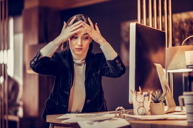 Vamos trabalhar. incrível trabalhadora de escritório sentada à mesa e tocando sua testa