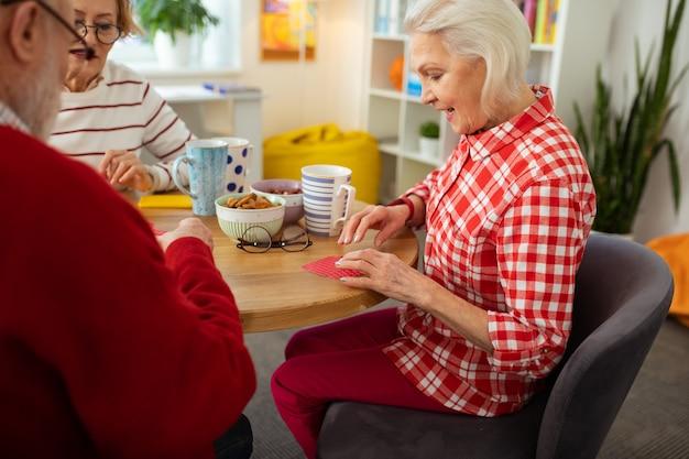 Vamos ver. mulher idosa empolgada pegando suas cartas enquanto olha para elas