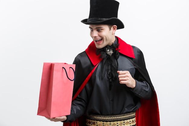 Vampire halloween concept - feliz bonito caucasiano vampiro segurando uma sacola de compras colorida na parede branca.