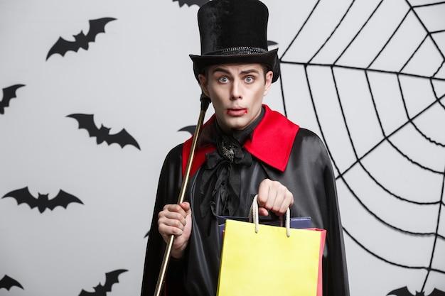 Vampire halloween concept - feliz bonito caucasiano vampiro segurando uma sacola de compras colorida.