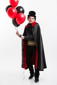 Vampire halloween concept - retrato de corpo inteiro de um vampiro caucasiano bonito em traje de halloween preto e vermelho.